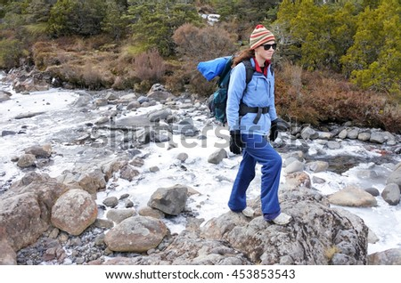 Woman hiker crossing a frozen stream in Tongariro National Park rain forest  in the North Island of New Zealand. Travel concept copy space