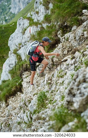Woman hiker with backpack walking a steep trail in the  mountains