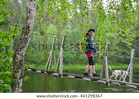 Woman hiking and crossing river over rope bridge
