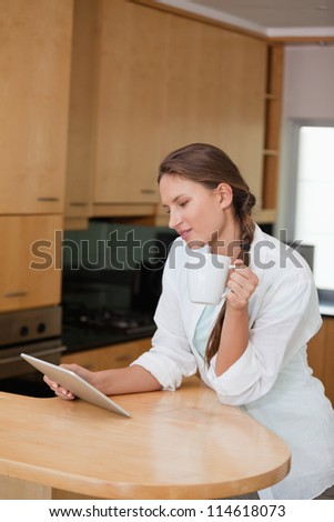 Woman holding a cup while looking at a tablet computer in a kitchen