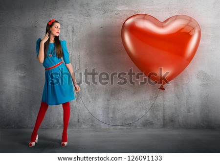 Woman holding a heart shaped balloon