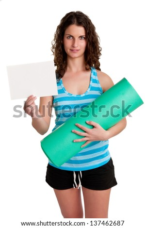 Woman holding a yoga mat and a white empty card, isolated in a white background