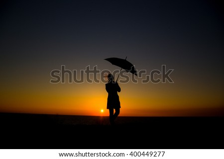 Woman holding and umbrella in silhouette against  orange sunset