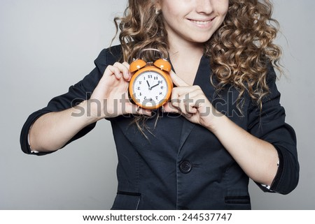Woman holding clock in hands over grey background