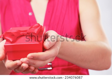Woman holding gift box isolated on white background.