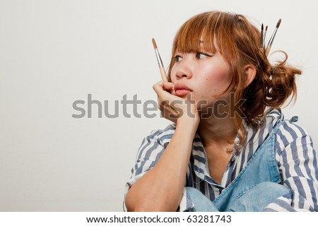 woman holding paintbrush looking pensive isolated over white background.