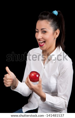 Woman holding red apple in hand and shows a raised finger