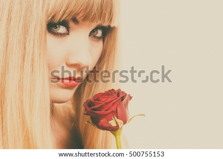Woman holding rose flower. Attractive blonde lady dark makeup studio shot toned image. Beauty, holidays, celebration concept