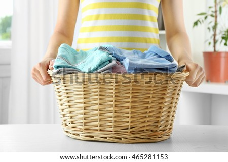 Woman holding wicker basket in laundry