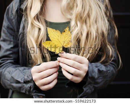 Woman holding yellow leaf