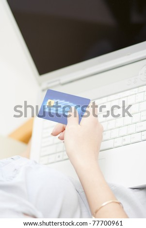Woman holds credit card while shopping online