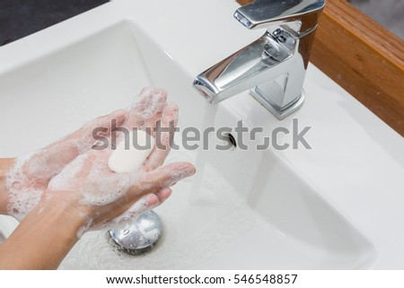 Woman in a bathrobe is washing hands with soap.