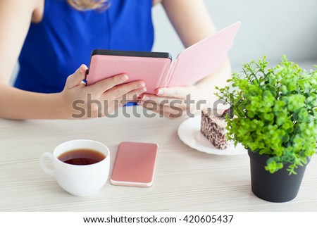 woman in a blue dress with pink phone reading the e-book in a cafe