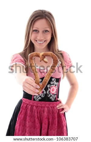 Woman in a colourful pink dirndl and apron holding out a heart-shaped pretzel