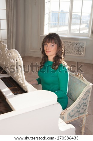 woman in a green dress plays on a white piano