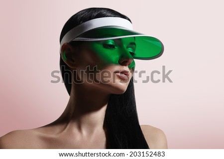 woman in a green sun visor on a pinky background