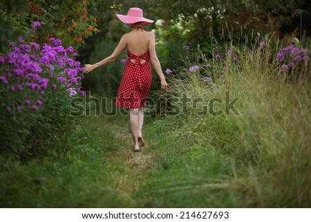 Woman in a hat walks among the beautiful flowers