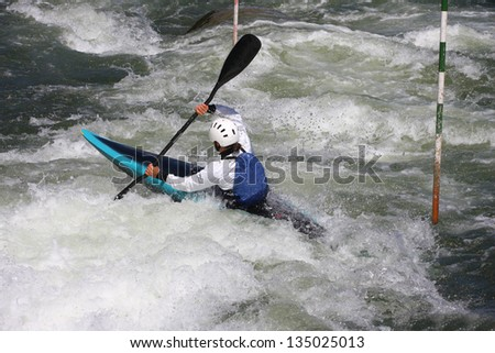 Woman in a kayak rowing against the tide