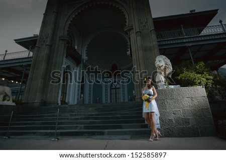 woman in a light white dress with a bouquet of yellow flowers posing near the palace
