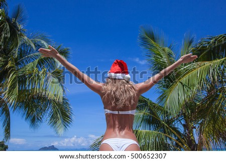 Woman in bikini celebrating Christmas on tropical beach with palms