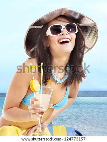 Woman in bikini drinking alcohol cocktail through a straw.