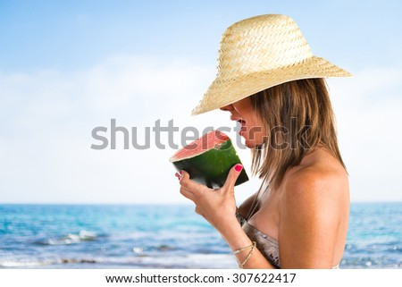 Woman in bikini eating a watermelon on unfocused background
