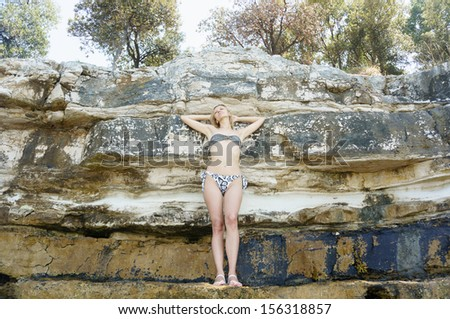 woman in bikini posing by the rocks