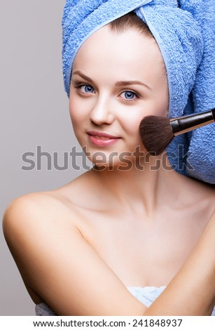 woman in blue bath towel on head with makeup brush