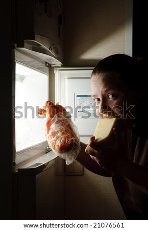 woman in front of the fridge eating cheese