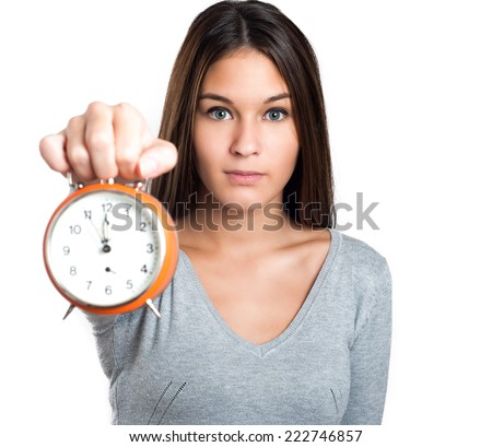 Woman in grey pullover showing the alarm clock isolated on white background