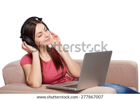 Woman in headphones enjoying music with closed eyes sitting on sofa with laptop, over white background