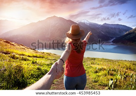 Woman in orange t-shirt and hat holding man by hand and going to the lake in the mountains at glowing sunrise