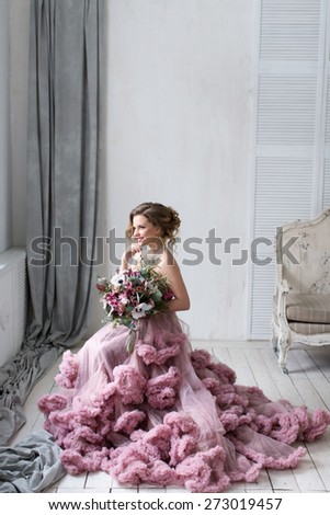 Woman in pink dress with a lush bouquet of flowers.