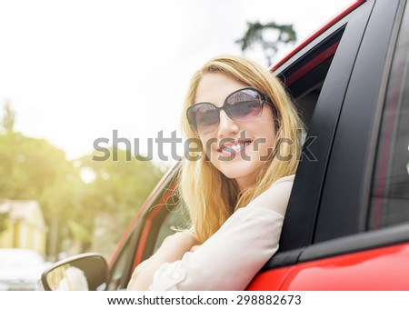 Woman in red car in sunglasses at sunset.