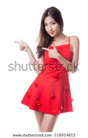 Woman in red dress pointing to copy space, isolated on white background