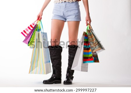 Woman in rubber boots and shorts. A lot of shopping.