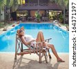 woman in the deck chair near the swimming pool - stock photo