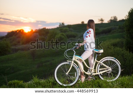 Woman in Ukrainian embroidery with bicycle standing at hill and looks at beautiful sunset with a blurred background of greenery