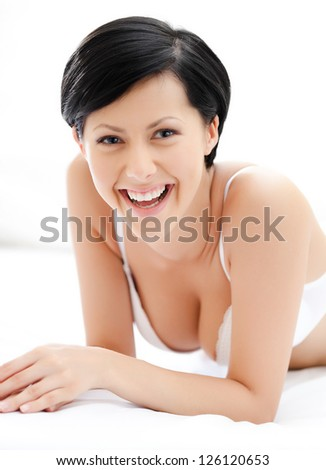 Woman in underwear is lying in the bed, isolated on white