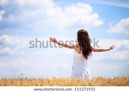 Woman in wheat field enjoying, freedom concept