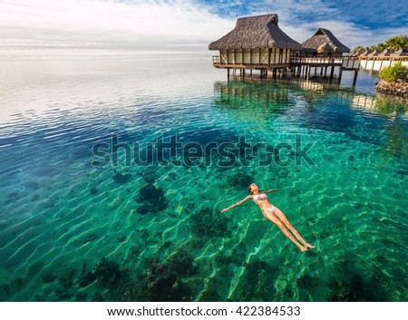 Woman in white bikini swimming in coral lagoon at the resort, Moorea, Tahiti