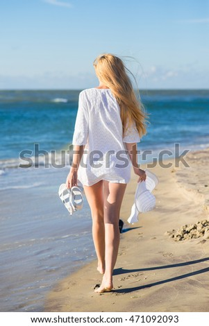 Woman in white dress walking on the beach. Back view