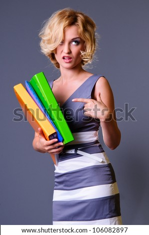 woman is dissatisfied with the work, points the finger at the working papers. on a gray background