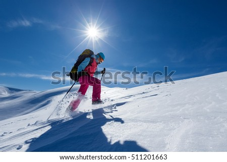 Woman is hiking in snowy winter mountains