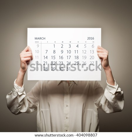 Woman is holding March calendar of the year two thousand sixteen.