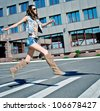 Woman is running down street - stock photo