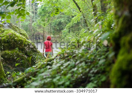 Woman is walking away to the beautiful, mysterious and green wood with red t-shirt