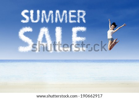 Woman jumping for summer sale at beach