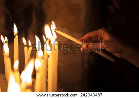 hand lighting. woman lighting candles in a church hand n