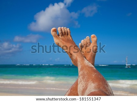 Woman long sexy legs against emerald sea and Caribbean beach background. Summer vacations concept.